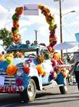 a man dressed as a skeleton walking next to a truck decorated in flowers in a parade