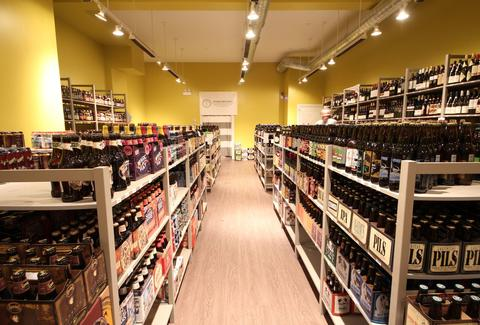 An aisle with shelves filled with beer bottles on both sides.
