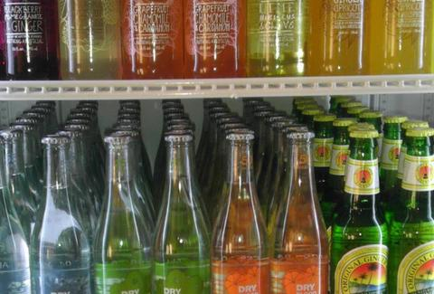 A shelf filled with colorful soda bottles.