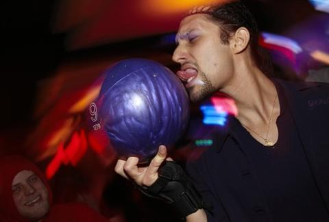 A man licking a bowling ball in a bowling alley.