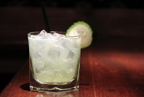 A clear cocktail with a cucumber garnish