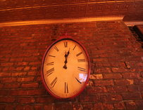 A giant clock hanging on a brick wall