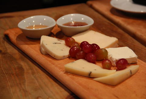 A cheese plate with grapes