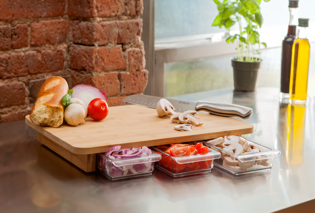 A cutting board with built-in storage containers