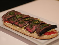 Pizza with steak atop it