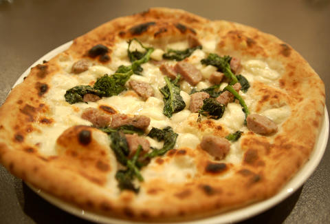 Pizza with sausage and greens