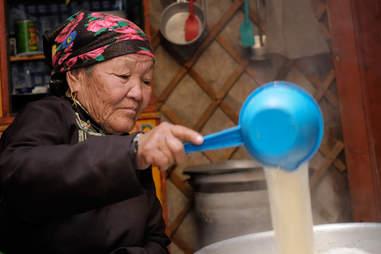 Mongolian woman making cheese
