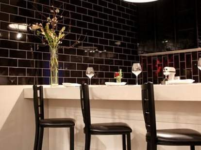 Black chairs and tables covered with white tablecloths.
