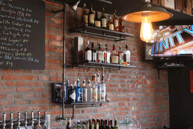 Cedar Point Bar & Kitchen's exposed brick barroom, with shelves built from pipes and TV broadcasting ESPN