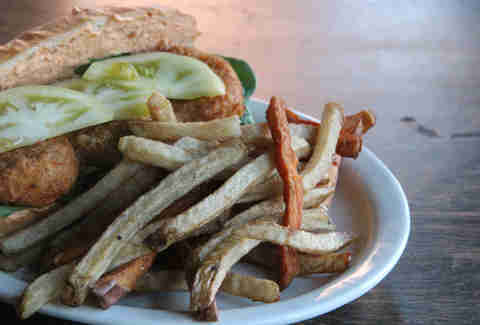 A pickled and fried green tomato po boy with sweet potato fries at Cedar Point Bar & Kitchen