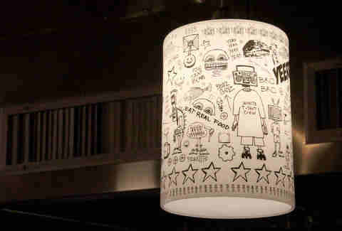 Street art-covered lamps hang over the noodle bar counter.