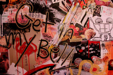 """Graffiti on the decoupaged back wall reads """"Get in my belly"""""""