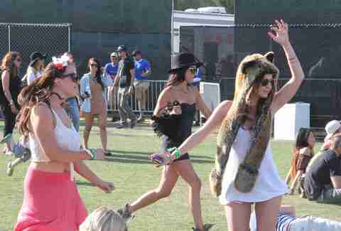 Two girls dance as another runs by at Coachella 2013