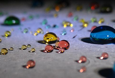 Colored beads of water on a flat surface