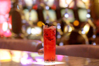 A bourbon blackberry collins lit by a spotlight on the bar at 28 West