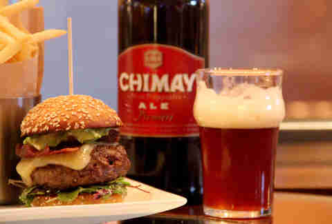 A beer-paired bacon and avocado cheeseburger beside a glass of Chimay Premiere at 28 West