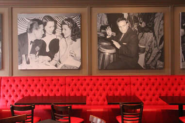 The upstairs red banquettes at Pennsylvania 6 lined with 1940s celebrity photos
