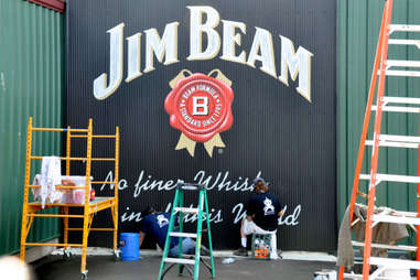 Painters finishing a Jim Beam sign on the stillhouse exterior