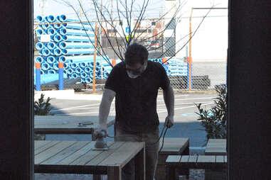 An employee sanding tables outside Rye in Louisville