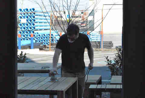 An employee sanding tables outside Rye in Louisville