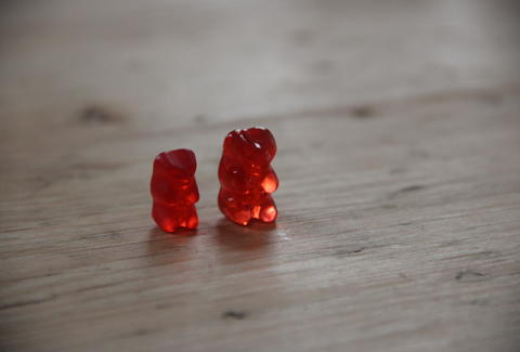 A regular gummy bear next to a vodka gummy bear