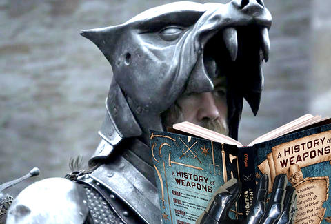 The Hound from Game of Thrones reads a History of Weapons