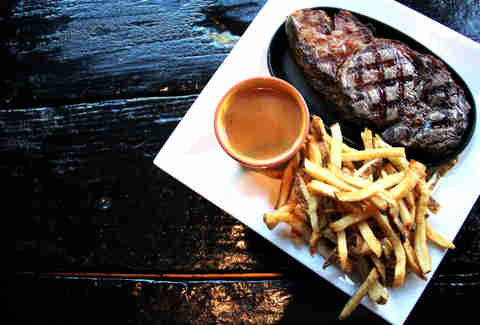 16oz ribeye steak with pommes frites and negro modelo cream sauce at Lucha Cartel