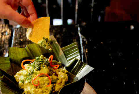 Dipping a chip into bacon guacamole at Lucha Cartel