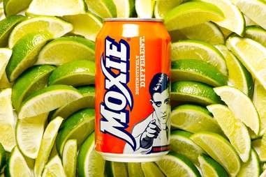 Can of Moxie soda on a bed of limes