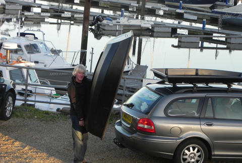 Boatpack being unloaded from the top of a car