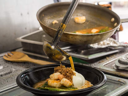 Prawns being ladled with sauce from DFG Noodles