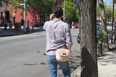 Man holding girlfriend's purse in Brooklyn