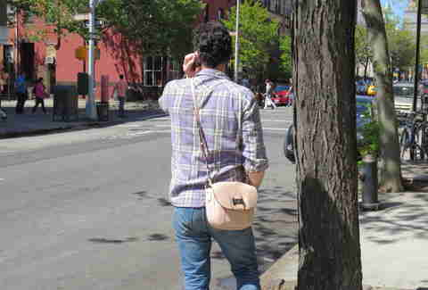 Man holding girlfriend's purse in Brooklyn