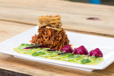A mountain of pulled pork topped with onion rings at Eden East