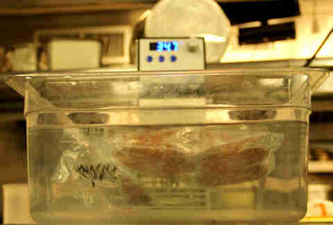 Sealed burger is slow-cooked sous vide in a water bath.