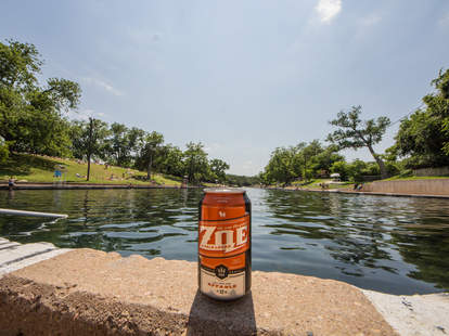A can of Hops & Grain's The One That They Call Zoe by a lake