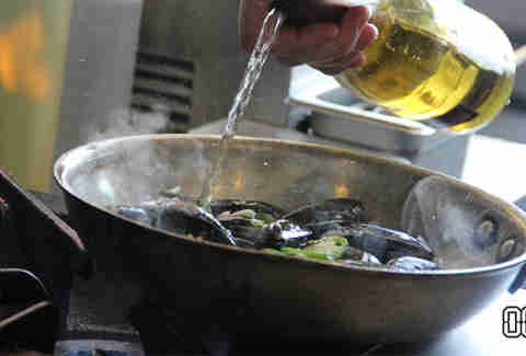 wine going in a pan full of mussels