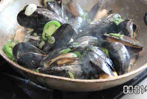mussels cooking in a pan with butter