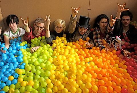 The crew of Top Office Machines in a ball pit at the studio