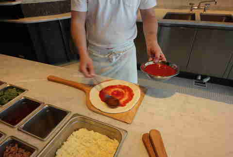 putting red sauce on a pizza at Pizzeria Locale Denver