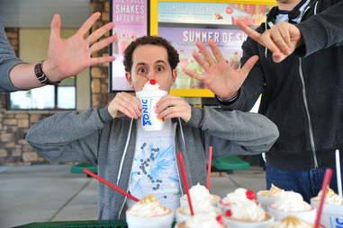 guy eats a caramel milkshake at Sonic