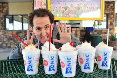 guy eats a hot fudge milkshake at Sonic