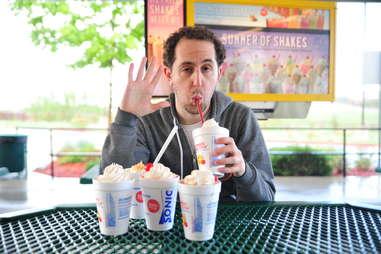 guy eats a pineapple milkshake at Sonic