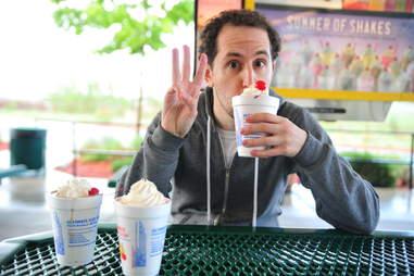 guy eats a cherry milkshake at Sonic