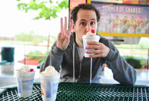 guy eats a cherry milkshake at Sonic