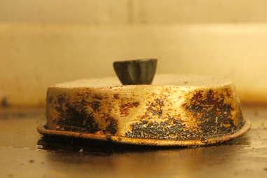 A pan lid helps PYT's lasagna bun burger cook faster.