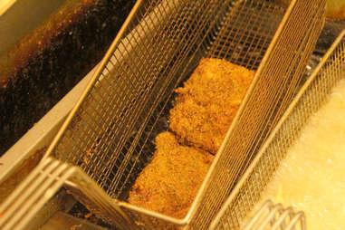 The lasagna bun burger wedges in the deep fryer at PYT.