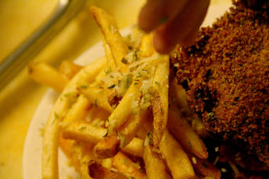 A plate of fries are seasoned with Italian spices at PYT