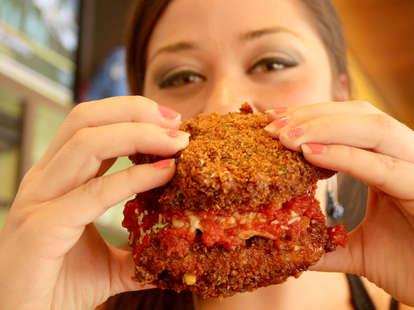 A girl attempts to eat the PYT Lasagna Bun Burger