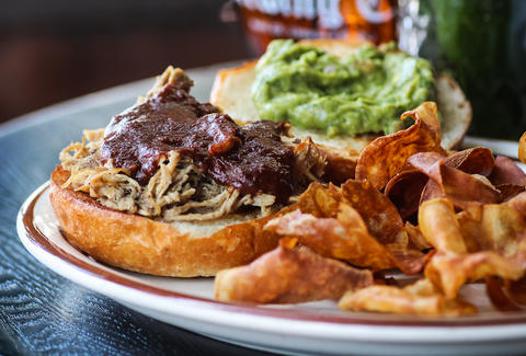 Pulled Pork Carnitas Sandwich with in house made mustard bbq sauce and guacamole.